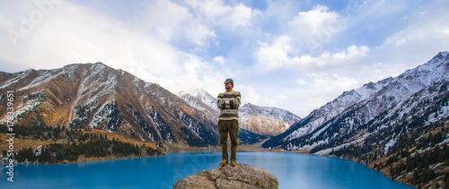 Plakat człowiek stoi na górze, górskie jezioro, lodowce. Duże jezioro Almaty, Kazachstan, Almaty