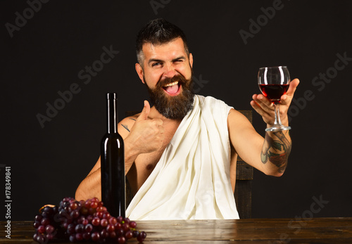 Sommelier tastes drink. Man with beard holds glass of wine Wallpaper Mural