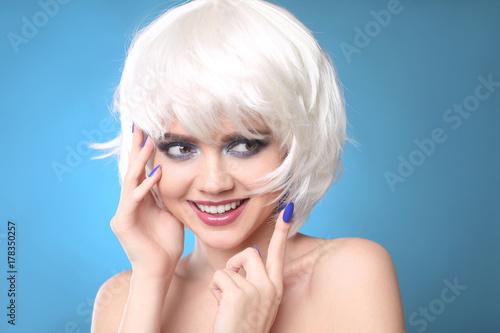 Plakat Zabawne uśmiechnięte blond. Makijaż. Zbliżenie piękna moda dziewczyna z Bob styl krótkie włosy i blask cień do powiek, wypielęgnowane paznokcie na niebieskim tle studio.