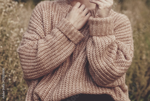Платно Closeup of woman wearing a beige soft oversized knitted sweater or jumper outdoors in the nature