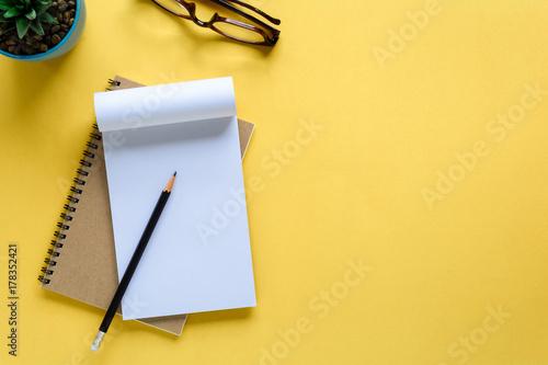 Obraz notebook and pencil on yellow desk - fototapety do salonu