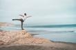 Man balancing on rock of ocean