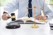 Judge gavel with scales of justice, male lawyers working having at law firm in office. Concepts of law