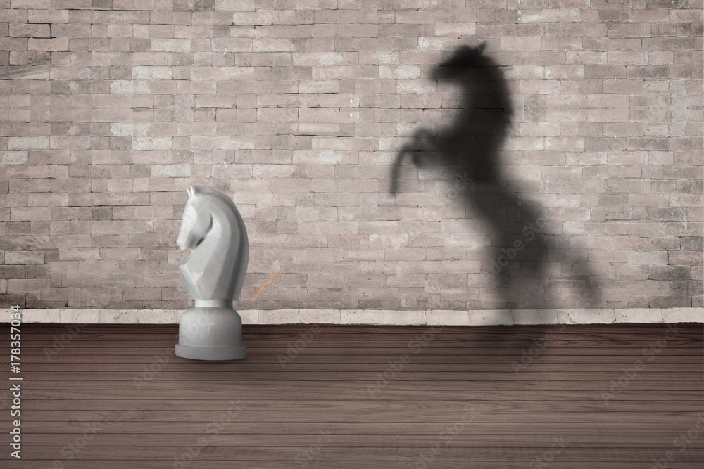 Fototapeta The concept of the hidden potencial. chess horse in the room which casts a shadow on the wall.