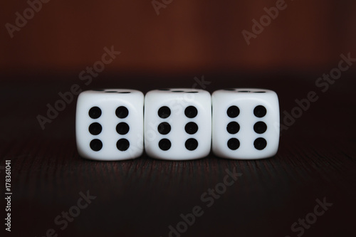 Photo Three white plastic dices in a row on brown wooden board background