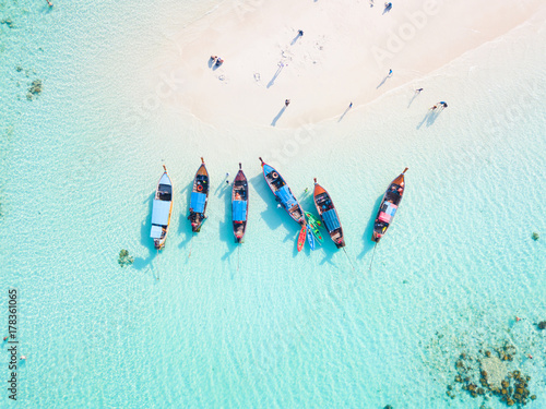 Fotografia Top view or aerial view of longtail boats on crystal clear water along the sand
