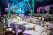 canvas print picture - Long dinner table decorated with white flowers, shiny candles and golden glasses stands in a beautiful hall
