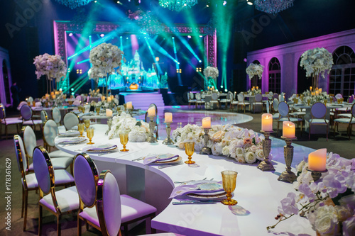 Long dinner table decorated with white flowers, shiny candles and golden glasses stands in a beautiful hall