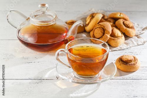 Plakat Domowe ciasteczka i filiżanka herbaty na stole w godzinach porannych