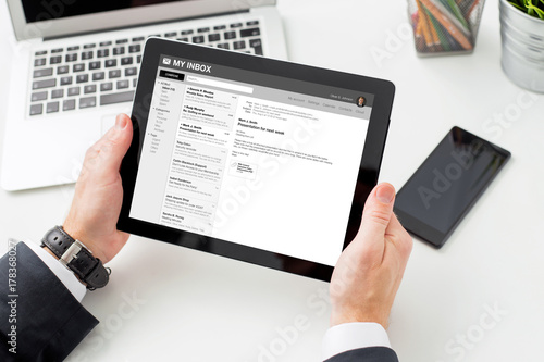 Businessman reading email on tablet computer.