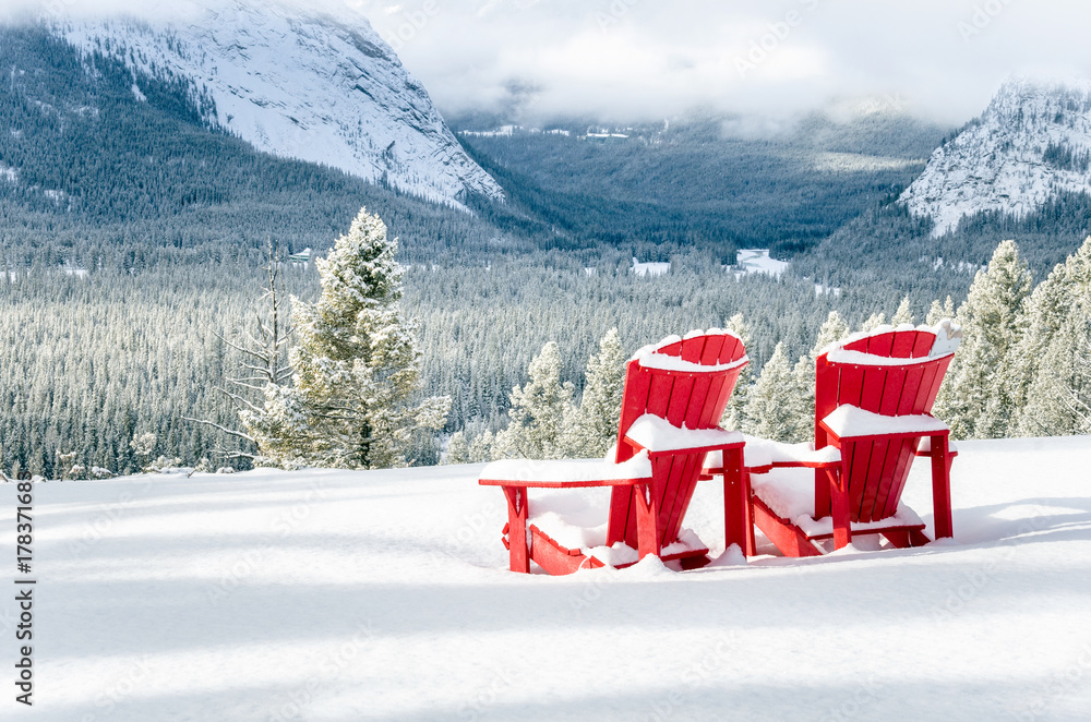 Fototapeta Snow Covered Red Adirondack Chairs Facing a Frozen Forested Valley on a Snowy Winter Day. Banff National Park, AB, Canada.
