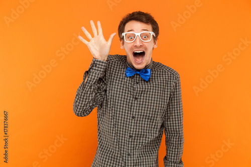 Fotografia, Obraz Well hi! Young adult crazy man toothy smiling and showing hand at camera
