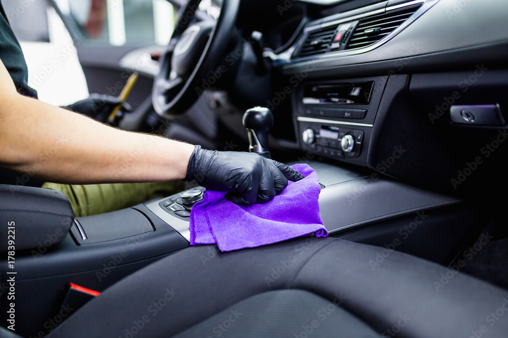 Obraz A man cleaning car interior, car detailing (or valeting) concept. Selective focus.  fototapeta, plakat