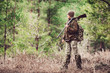 canvas print picture - Female hunter in camouflage clothes ready to hunt, holding gun and walking in forest.