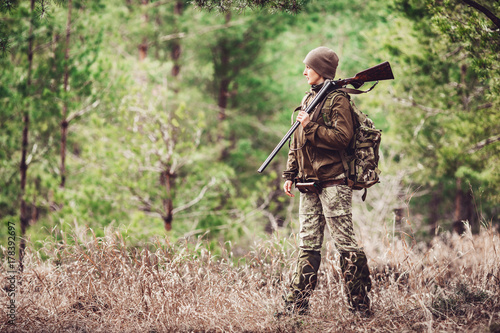 Fotografering Female hunter in camouflage clothes ready to hunt, holding gun and walking in forest
