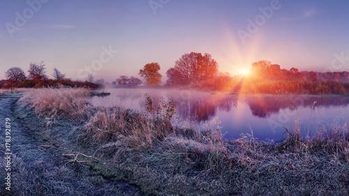 Obraz Sunrise on autumn frosty nature. Landscape of bright dawn over river. grass with hoarfrost shining on sun lights - fototapety do salonu