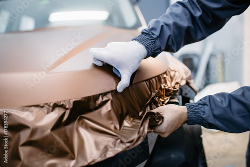 Fotografía  Car wrapping specialist putting vinyl foil or film on car.
