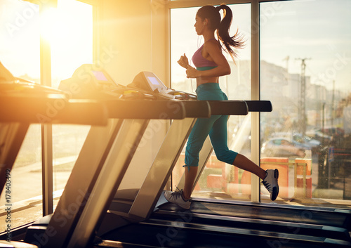 Fototapeta Young healthy athletic woman running on a treadmill near the sunny window in the gym and listening music