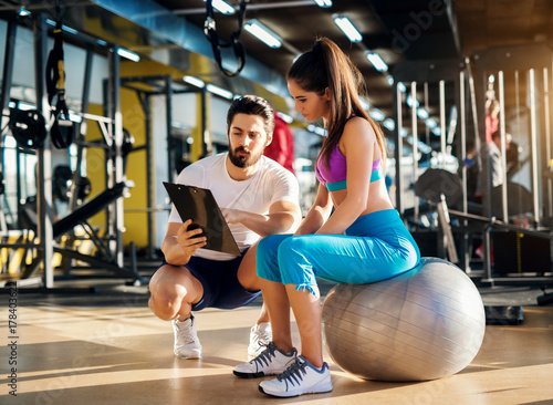 Fototapeta Young healthy active woman sitting on the gym ball and consulting with a  personal trainer about an exercise plan