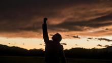 Man Raising His Fist Against Sunset Sky