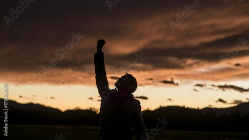 Fotomural  Man raising his fist against sunset sky