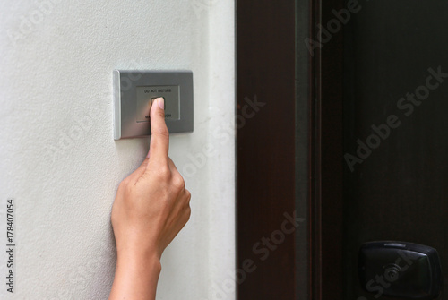 Foto  Close up of hand ringing doorbell.