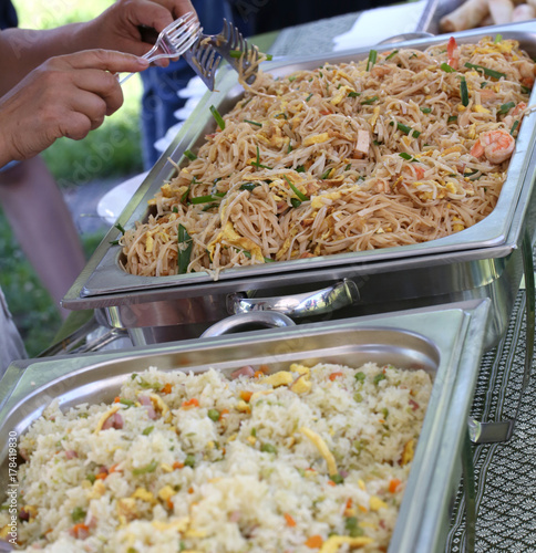 cook prepares noodles trays with vegetable and egg and shrimp