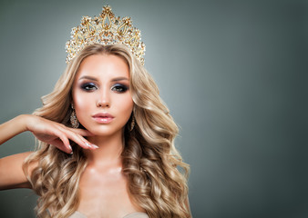 Glamorous Blonde Woman with Golden Crown, Makeup and Wavy Hair. Cute Fashion Model with Diamonds Jewelry, Shiny Curly Hairstyle and Make up