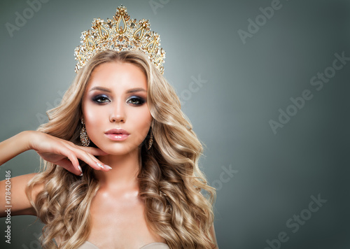 Fototapeta Glamorous Blonde Woman with Golden Crown, Makeup and Wavy Hair. Cute Fashion Model with Diamonds Jewelry, Shiny Curly Hairstyle and Make up obraz