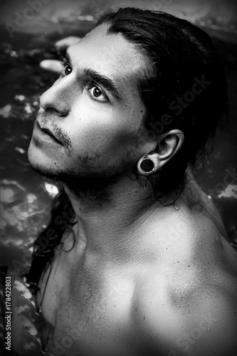 Photo  A handsome guy with long hair and piercings on waterfalls in a rain forest