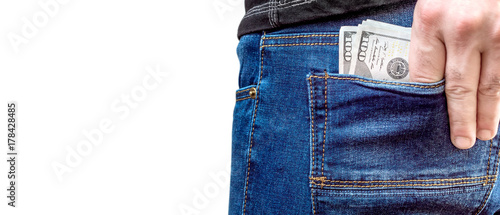 Fotografía  A man puts money in the back pocket of jeans. Isolated on white.