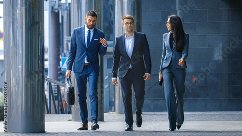 Foto Male and Female Business People Walk and Discuss Business