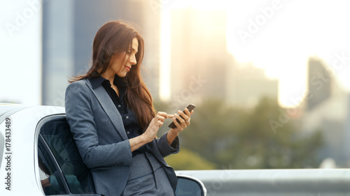 Fotografia  Business Woman Uses Smartphone While Leaning on Her Premium Class Car