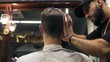 Back view of a young man getting his hair cut sitting in the chair at the barbershop. Barber cuts the hair of the client with clipper or trimmer in slow motion
