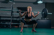 Crossfit Muscular strong woman crouching with heavy weight in the gym