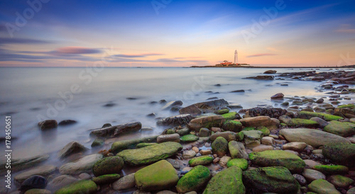 Foto op Plexiglas Kust Long exposure of the sea and rocks surrounding St.Mary's Lighthouse on the Northumberland coast, England