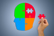 Hand inserting missing jigsaw in man's head shape, business or health care concept