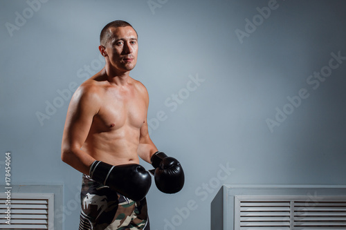 handsome man or healthy boxer or Thai boxer with six pack wearing boxing gloves Wallpaper Mural