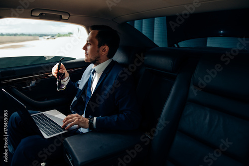 Fotografia Serious businessman in a car with laptop