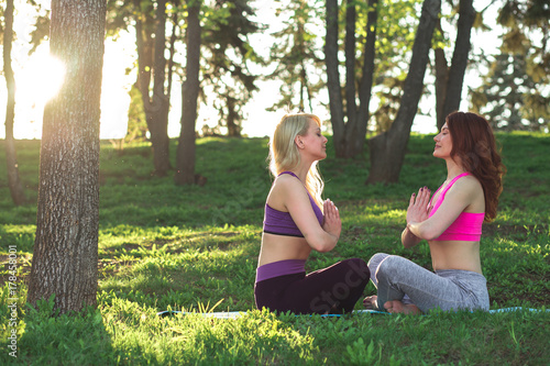 Plakat dwa Młoda kobieta robi joga plenerowy w parku
