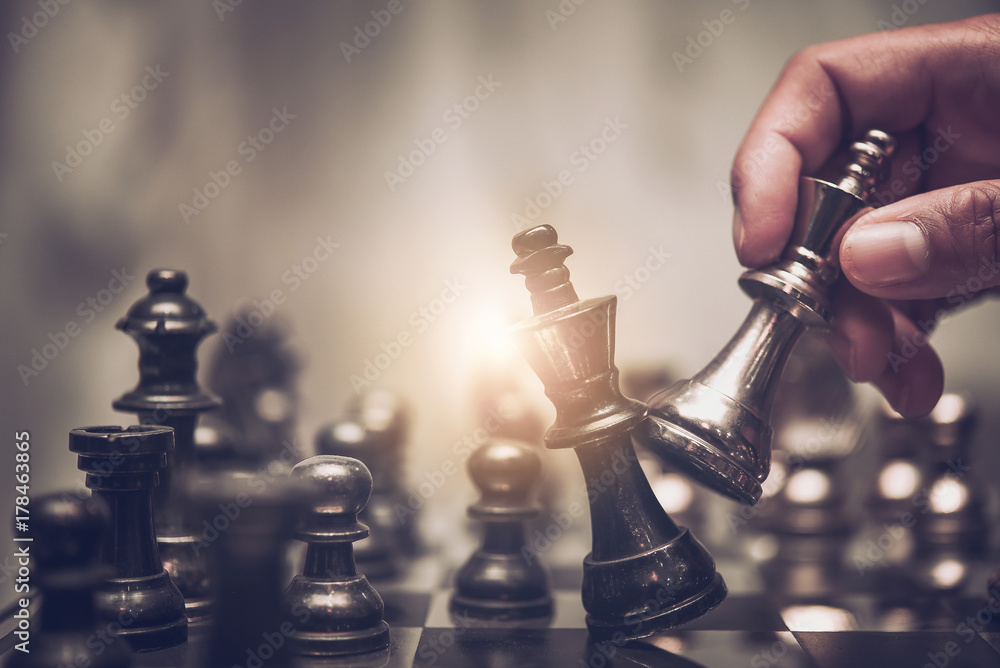 Fototapeta Businessman moving chess piece on chess board game concept for ideas and competition and strategy, business success concept, business competition planing teamwork strategic concept.
