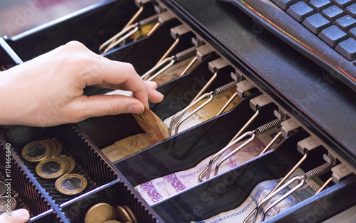Saleswoman hands at cash register with brazilian money notes and coins inside th Canvas Print