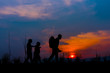 Group of happy children playing on meadow at sunset, silhouette