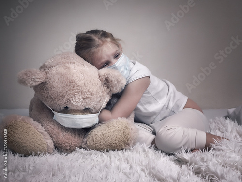 Fotografía  Little girl and big plush bear in medical masks