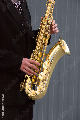 Plakat Ręki fornal bawić się na saksofonie na szarym tle