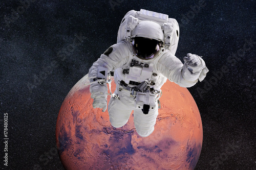 Fototapeta astronaut performing a space walk around the red planet Mars