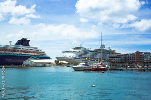 Plakat widok na molo z kilku dużych statków i kilka łodzi na niebieskim tle nieba