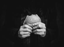 The Concept Of Hunger And Poverty. A Roll Or Hamburger In The Hands Of A Close Up. Black And White Monochrome Photography.