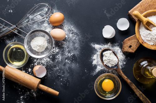 Zdjęcie XXL Składniki do pieczenia. Miska, jajka, mąka, jaja, wałkiem i skorup jaj na czarnej tablicy z góry.