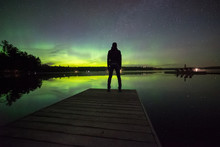 Man Standing At The End Of A Dock Looking At The Aurora Borealis Over A Lake During The Night.